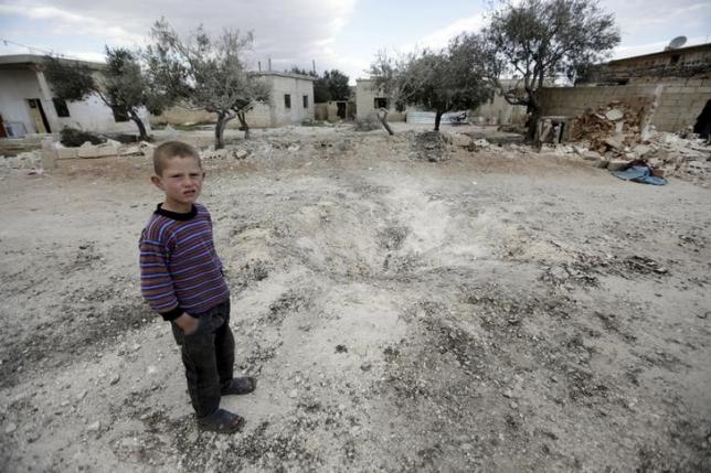 A boy stands near a hole in the ground after a shell fell in the rebel-held town of Jarjanaz, southern Idlib countryside, Syria March 5, 2016. REUTERS/Khalil Ashawi